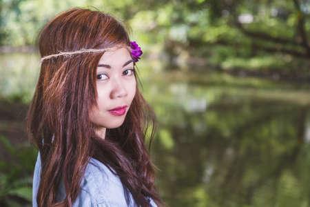 Filipina woman with a garden bokeh looking at camera Zdjęcie Seryjne