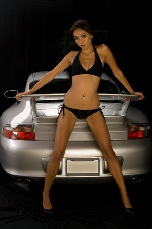 Young brunette girl with metallic silver car