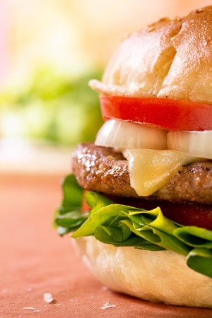 Close-up vertical shot of one side of cheeseburger on table  Stock Photo - 13659966