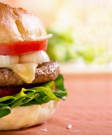 american cuisine: Close-upl shot of right side of a cheeseburger on table  Stock Photo