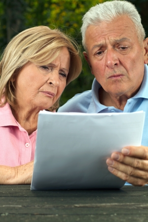 finance problems: Retired citizens reading papers with expression on their faces