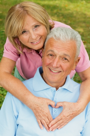 Healthy senior couple in park. Female showing heart symbol on his chests. Stock Photo