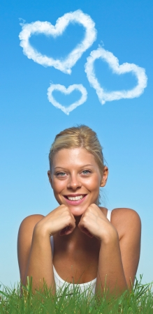 Beautiful blue-eyed blonde with cloudy love hearts  photo