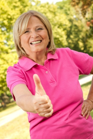 Beautiful senior lady showing thumb-up in a polo-shirt