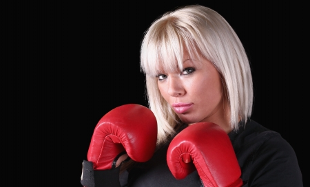 stance: Attractive blonde female kick-boxer posing