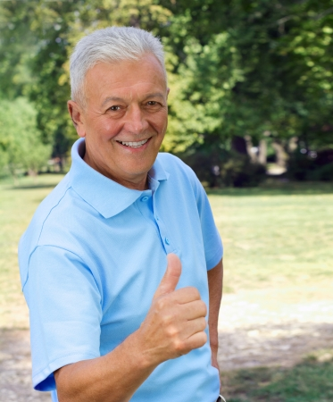 Senior showing thumb-up outdoors. See more of this model Stock Photo - 17752727