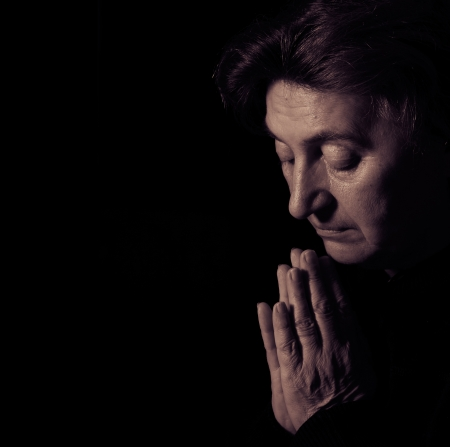 Senior female prayer. Low-key studio lighting. photo