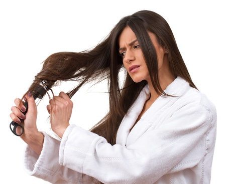 hair problem: Young beautiful girl having problems while hair  Isolated studio shot