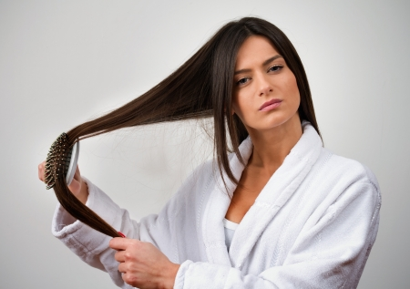 combing hair: Young female combing long hair on gray background  See more of this model Stock Photo