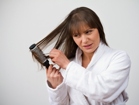 Female losing hair while combing  Problems caused by hormonal therapy Stock Photo - 18036331