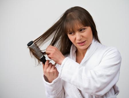 causaba: Mujer perdiendo el cabello peinado en tanto que los problemas causados ??por la terapia hormonal