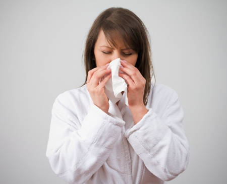 Women blows nose in bathrobe on grey background. See more Stock Photo - 18122800