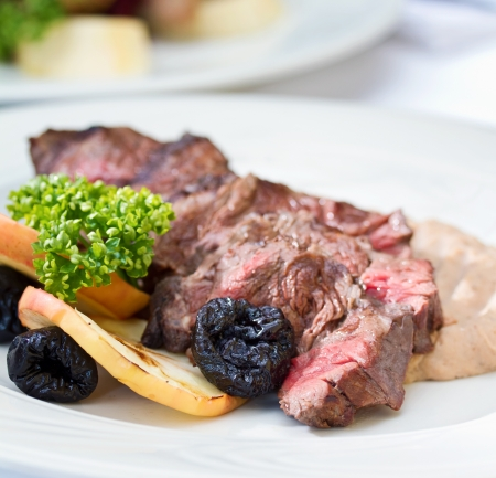 Venison steak cuts on a chestnut puree with dried plums and grilled apple slices Stock Photo