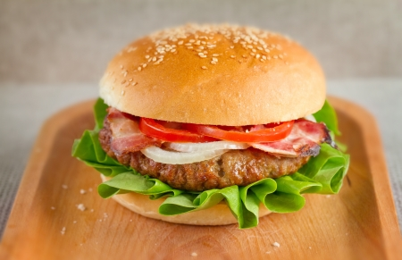 The hamburger, a ground beef patty between two slices of bread with lettuce, onion, bacon and tomato on wooden plate Stock Photo