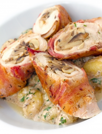 Chicken bacon roulade, chicken breasts, pounded thin, stuffed with bacon, shallots, and Parmesan, rolled up, browned, roasted, then served sliced on gnocchi