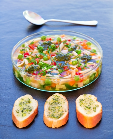 minestrone: Rich minestrone soup in glass plate, served on stone with garlic bread Stock Photo