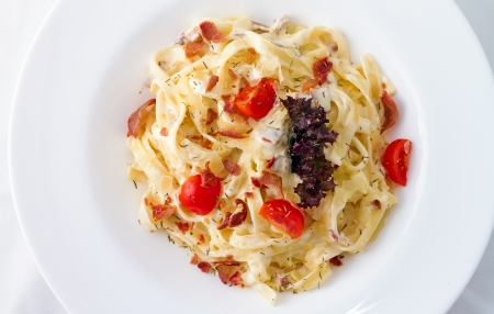 Carbonara is an Italian pasta dish  and more specifically to Rome, based on eggs, cheese (Pecorino Romano or Parmigiano-Reggiano), bacon (guanciale or pancetta), and black pepper. photo