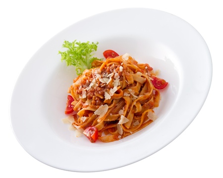 Colorful plate of pasta bolognese with some fresh tomato, parmesan and green salad photo