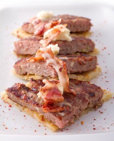 beefburger: Pre-sliced traditional burger patty called pljeskavica, served on pita bread with some cream cheese and grilled bacon. Sprinkled with hot pepper flakes Stock Photo