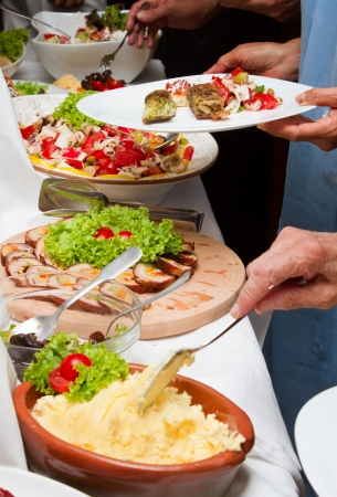Celebration event with catering table and people hands with plates