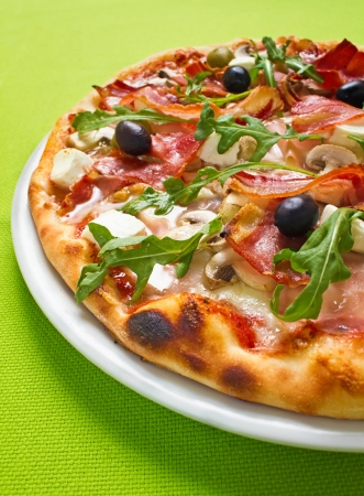 arugula: Close up shot of a fabulous rustic pizza on a vivid green background Stock Photo