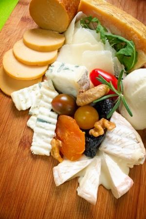 tabla de quesos: Variedad de productos lácteos Elección de queso sobre tabla de madera del techo plano