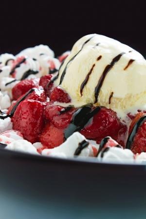 large ball: Vanilla ice cream on freshly glazed strawberries on dark background