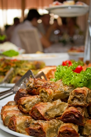 Close up shot of stuffed pastry rolls on a banquet table with people in background photo