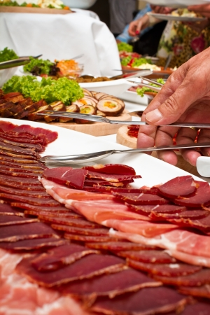 Human hand holding tongs over plate of sliced smoked meat photo