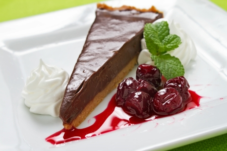 chocolate slice: Chocolate tart, also known as chocolate cream pie, is a dessert consisting of dark chocolate, cream and eggs, beaten together, poured into a crisp, unsweetened puff pastry shell and baked until firm Stock Photo
