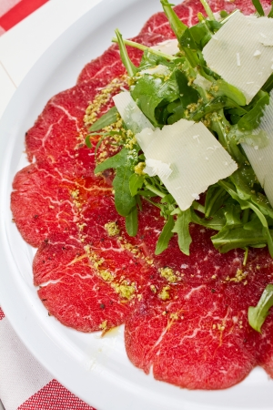 thinly: Carpaccio is a dish of raw meat  (such as beef, veal or venison), thinly sliced or pounded thin and served mainly as an appetizer.