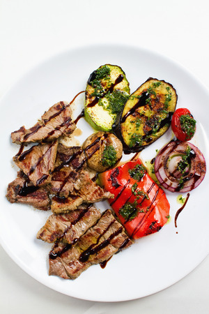 overhead shot: Grilled flank beef steak with grilled vegetable on white plate. Overhead shot