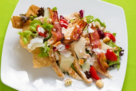 chicken salad: Salad of romaine lettuce and croutons dressed with parmesan cheese, lemon juice, olive oil, egg, Worcestershire sauce, garlic, and black pepper mixed with grilled chicken and pan fried bacon Stock Photo
