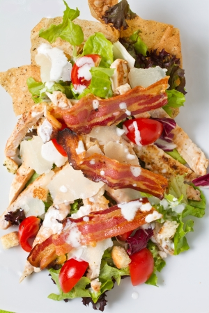 Salad of romaine lettuce and croutons dressed with parmesan cheese, lemon juice, olive oil, egg, Worcestershire sauce, garlic, and black pepper mixed with grilled chicken and pan fried bacon photo