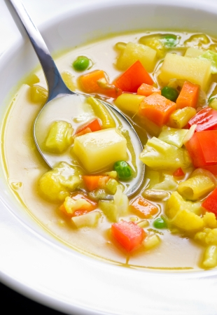 Close up shot of vegan soup with visible vegetable chunks and spoon Stock Photo