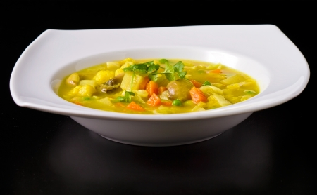 Vegan soup plate on black with blurred reflection photo