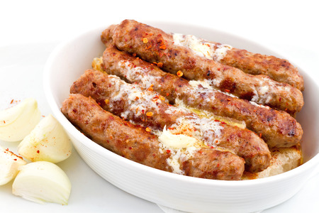 Cevapcici  Kebab  served on a half bun tossed with some  kaymak  cream cheese and freshly chopped onions