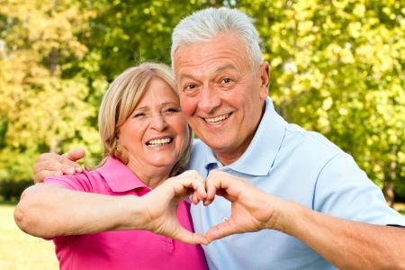 pareja saludable: Senior pareja sana que muestra el coraz�n y la sonrisa al aire libre