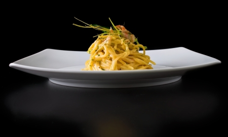 Nicely served spaghetti carbonara on black background with small reflection below