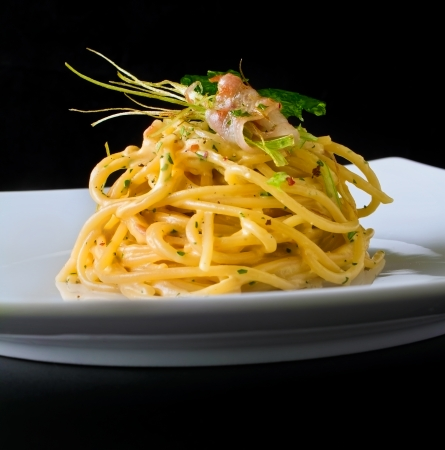 Nicely served spaghetti carbonara on black background with arty garnish