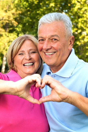 Senior healthy couple showing heart and smiling outdoor. Valentine`s day concept