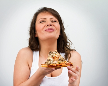 Young adult female enjoy eating fresh pizza on grey background photo