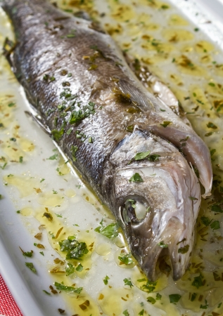 sea bass: Oven roasted sea bass in rich brine from white wine, olive oil and parsley