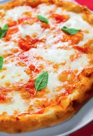 Close up shot of freshly baked Margherita pizza. Simply cheese, tomato sauce and basil leaves Stock Photo
