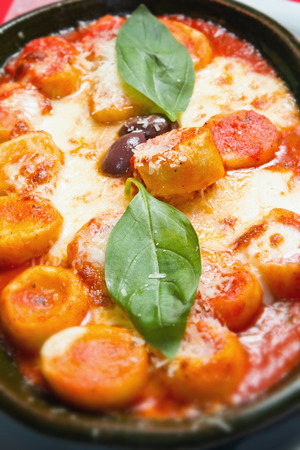 Vertical closeup shot of Gnocchi in rich marinara sauce with fresh basil leaves and black olives. Subtle copy space bellow. See more italian food photo