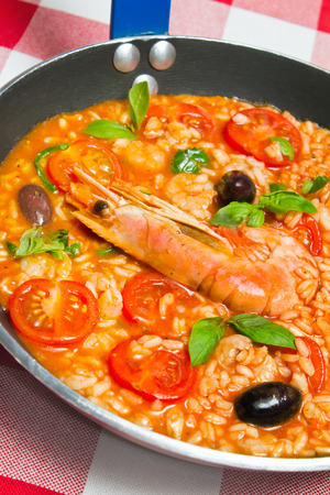 Risotto con Gamberi, or Rice with Prawns in skillet pan for one person. See more Italian food photo