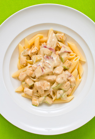 alfredo: Overhead shot of penne pasta with alfredo sauce, bacon and zucchini Stock Photo