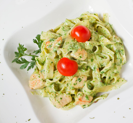 Tasty rich Pesto Chicken tagliatelle pasta with cherry tomato and fresh parsley Stock Photo