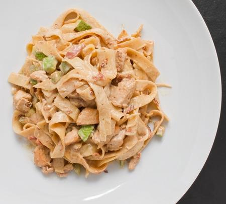 alfredo: Tagliatelle Chicken Pasta creamy cheese sauce and zucchini on white plate. Overhead shot
