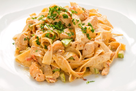 sideway: Tagliatelle Chicken Pasta creamy cheese sauce and zucchini on white plate. Sideway shot Stock Photo